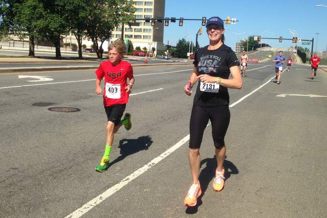 Reinhardt Harrison closes in on world record in the half marathon for 10-year-olds at the Alexandria Running Festival Half Marathon May 26, 2014, escorted by his mother, Heidi Johannesen.