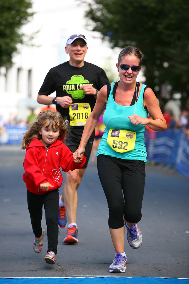 Selina Read gets some last-minute company across the Parks Half Marathon finish line, while Rob Kennedy thanks his lucky stars the newcomer isn't in his age group. Photo: Dan Reichmann, MCRRC