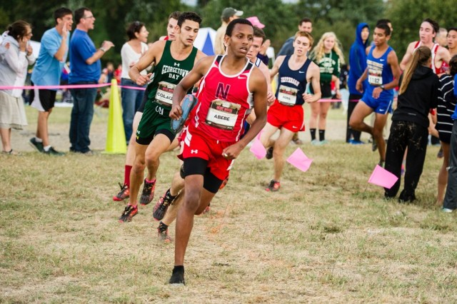 Northwood's Michael Abebe carries his shoe through the senior race. Photo: Marleen Van den Neste