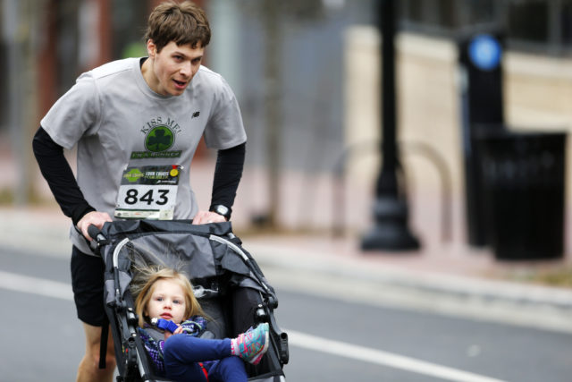 Adam Schwaber pushes his daughter Julia up Wilson Boulevard at the end of the Four Courts Four Miler.