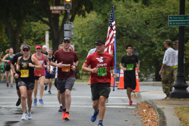 Brian Butler, of York, Pa., carries the flag in the sixth mile of the Army Ten-Miler. Photo: Charlie Ban